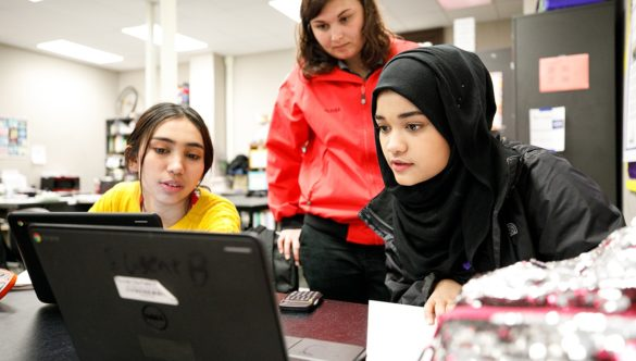 AmeriCorps member stands behind two students as they work at laptops in the classroom