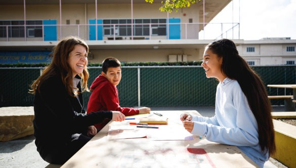 city year americorps member sitting with two students doing work as they sit at a large table outside in the school courtyard
