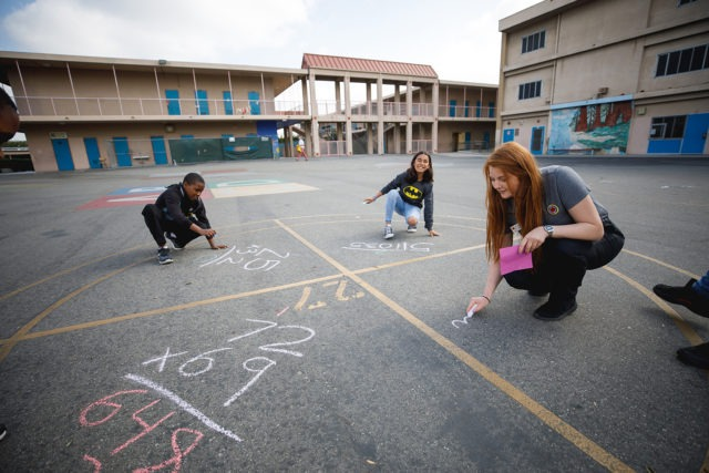 city year americorps member and student drawing out math problems with chalk on the black pavement in a school courtyard