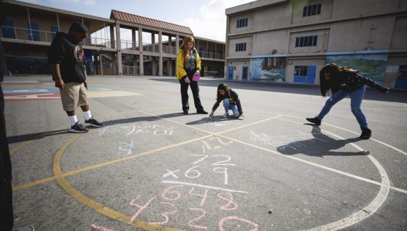 students are doing math problems in chalk on playground with AmeriCorps member