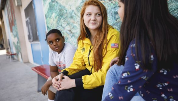 AmeriCorps member talks with student on bench while another listens
