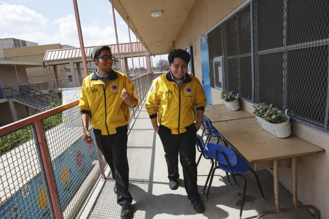 two AmeriCorps members walk together through hallway in conversation