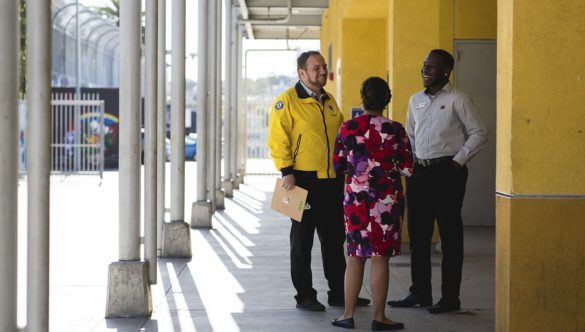Two AmeriCorps members speak with a school administrator.