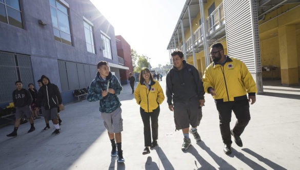 Two male middle school students walk alongside two City Year AmeriCorps members outside school on a sunny day