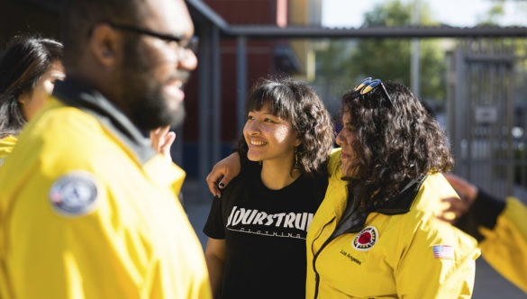 A middle school student stands with her arm around her City Year AmeriCorps member