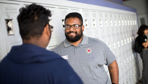 city year americorps member talking with a high school student as they stand in front of lockers in a school hallway