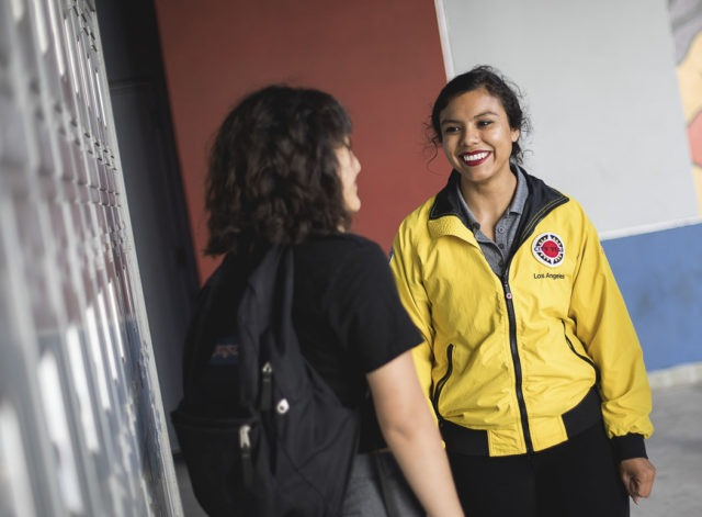 An AmeriCorps member talking with a student in front of lockers