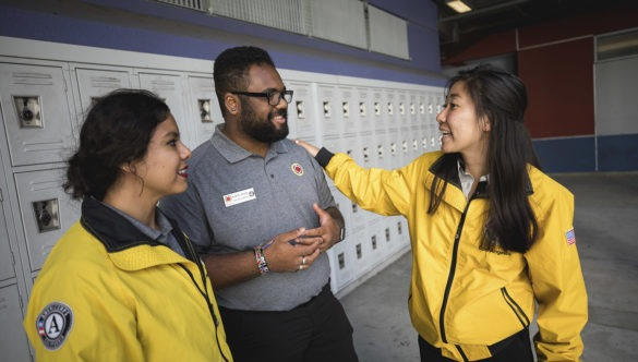 Three AmeriCorps members standing in front of lockers, talking