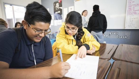 An AmeriCorps members sits at a desk with a student, pointing at his worksheet
