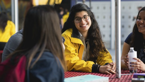 A City Year AmeriCorps member sits in an outdoor table with a small group of students