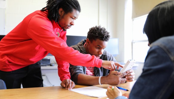 a city year americorps member is standing over two students who are sitting at a desk and showing one of them a word in a book the student is reading