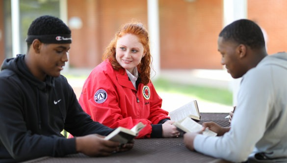 city year americorps member sitting with two high school students- all sitting at a table outside reading books