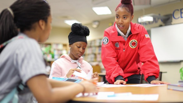 city year americorps member stands and helps two students who are sitting at a table working on schoolwork