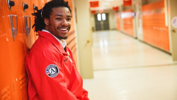 An AmeriCorps member leans again lockers in a school hallway.
