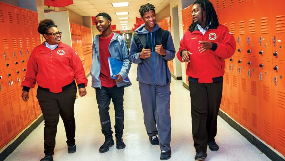 two AmeriCorps members are walking and talking with two high school students in the hallway