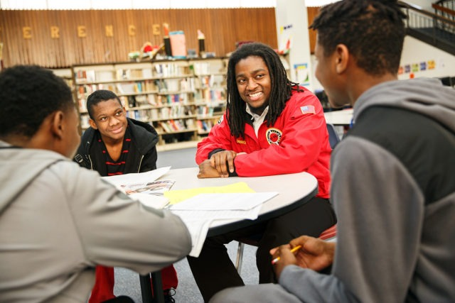 City year americorps member with three students sitting at a table in a school library