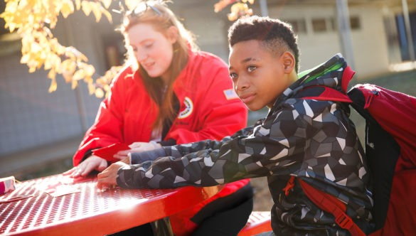 City year americorps member and a student with a backpack sitting at a table in a school courtyard in the sunshine