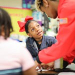 a student looks up at an AmeriCorps member as they help them at their desk