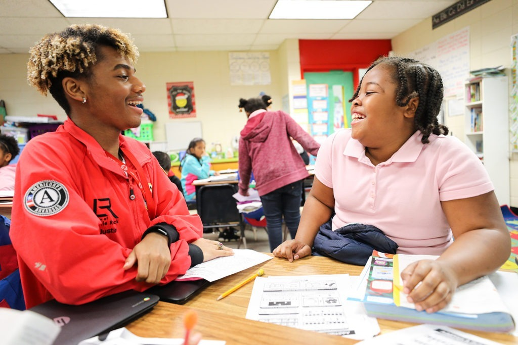AmeriCorps member and student are smiling and laughing together as they do work at a table in the classroom