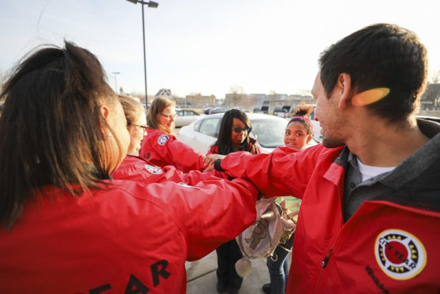 The camera looks over two City Year AmeriCorps members' shoulders as they put their hand in for a spirit break