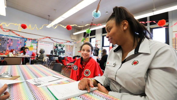 city year americorps member sits with a student wearing a red city year jacket as they read together in a classroom