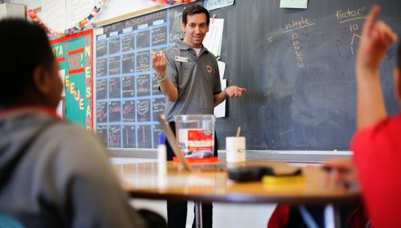 city year americorps member standing in front of a chalkboard showing multiples as students watch