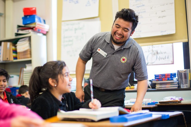 city year americorps member laughing with a student who is sitting at a desk and writing in her book