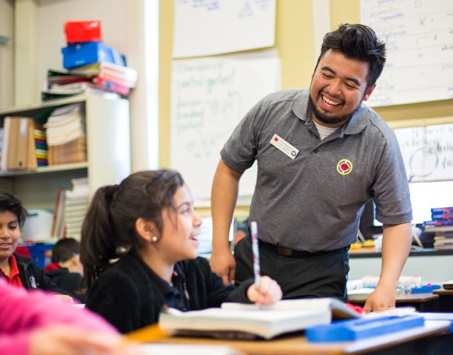 A smiling AmeriCorps member works with a student helping her with her textbook at her desk in a classroom