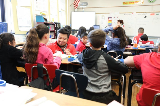 city year americorps member kneeling at a students desk in a full classroom while a teacher teaches