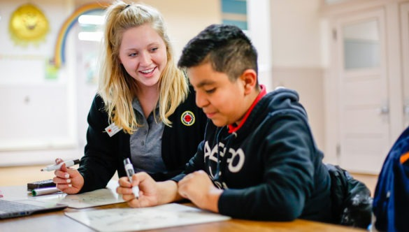 city year americorps member sitting next to a student as he does his work at a desk