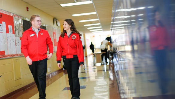 two city year americorps members walking down a school hallway next to lockers