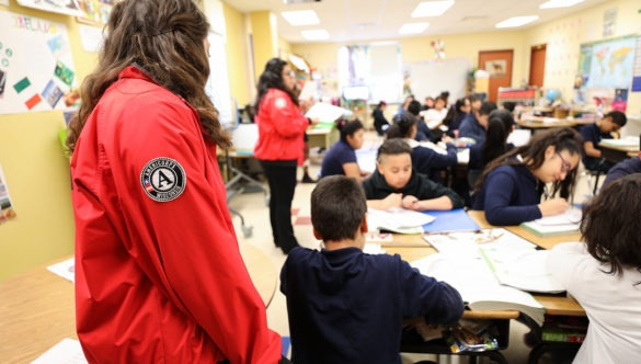city year americorps members in a classroom helping students who are working with their desks pushed together
