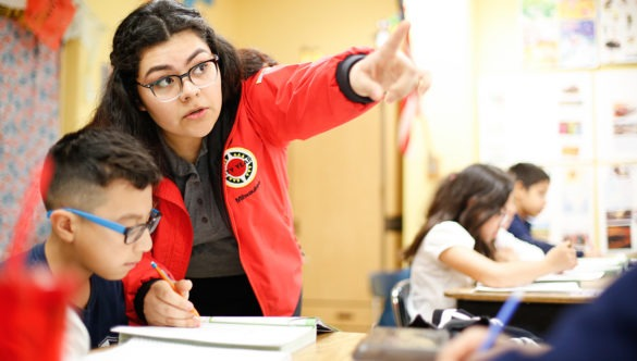 city year americorps member pointing at something as a student looks on