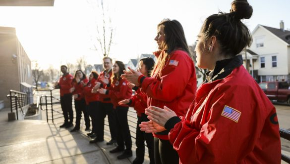 A team of 12 City Year AmeriCorps members stand in a straight line, clapping to welcome their students to school
