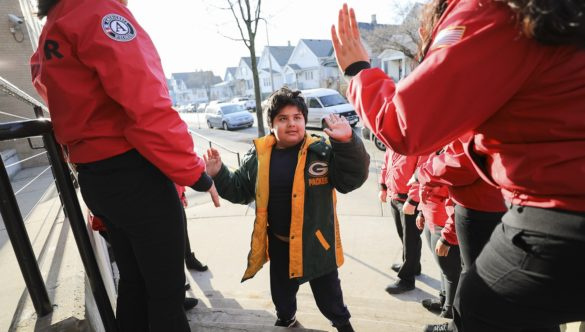 A young student in a winter coat high-fives two City Year AmeriCorps members