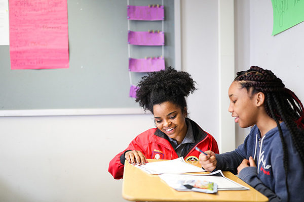 City Year AmeriCorps member kneeling next to a student at a desk as they review work