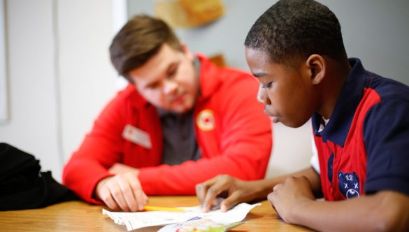 city year americorps member sits with a student at a desk as they review work