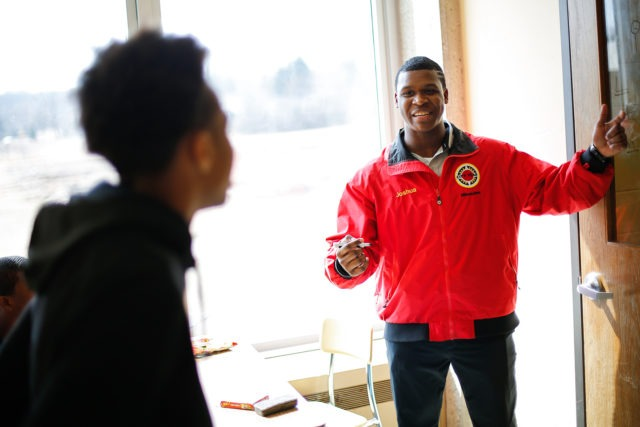 city year americorps member explains a lesson to a student as they stand facing a chalkboard
