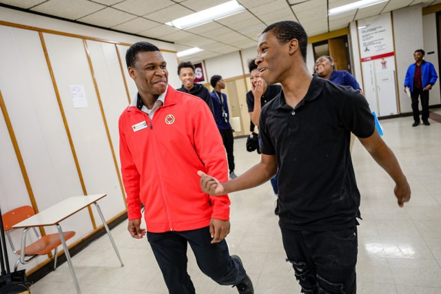 AmeriCorps member walking and laughing with a high school student