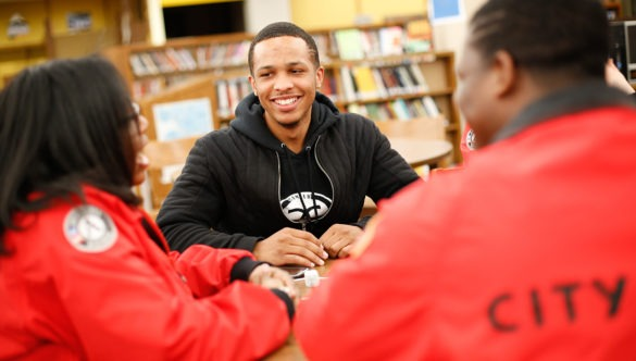 two AmeriCorps members talking with a high school student at a table in the library