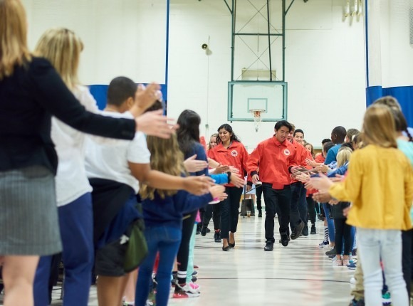 AmeriCorps members coming down a line up of students in a gymnasium giving the students high fives