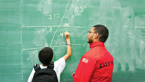 City year americorps member and a student with a back pack at a classroom chalkboard as the student solves math problems