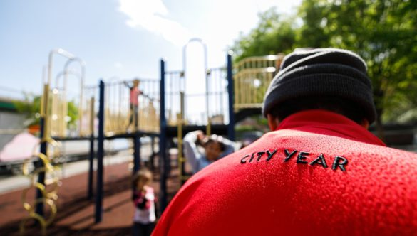 AmeriCorps member is on playground with students while they play