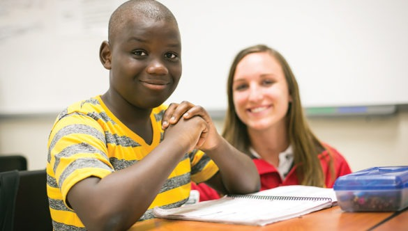 A student smiling for the camera in a classroom while a City year americorps member looks at the camera in the background