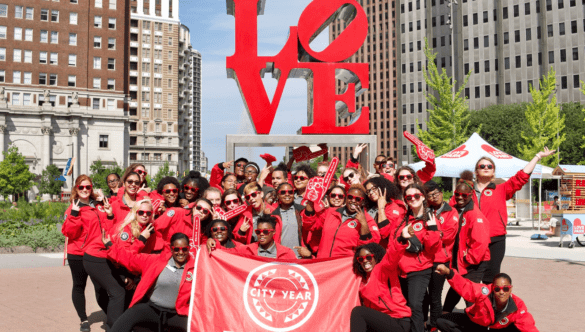 Philadelphia AmeriCorps members with flag at LOVE sign