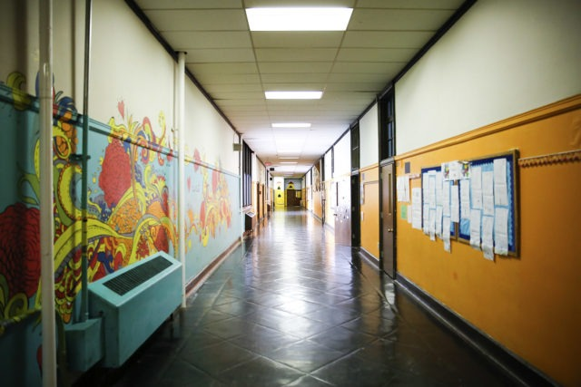 A school hallway with murals and bulletin boards.
