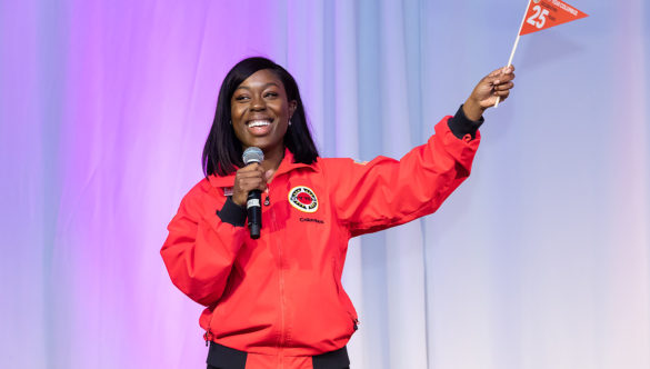A smiling AmeriCorps member waves a pennant on stage