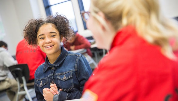 A young girl in a classroom taking with a City Year Americorps member