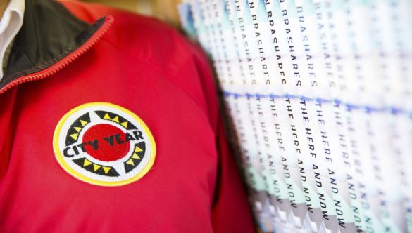 close up of AmeriCorps members' jacket, standing next to a row of books