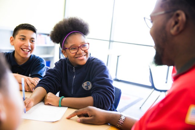 Two students writing at a table with a City Year mentor.